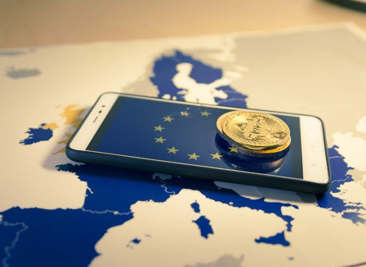 Map of Europe with a smartphone and coin placed on top.