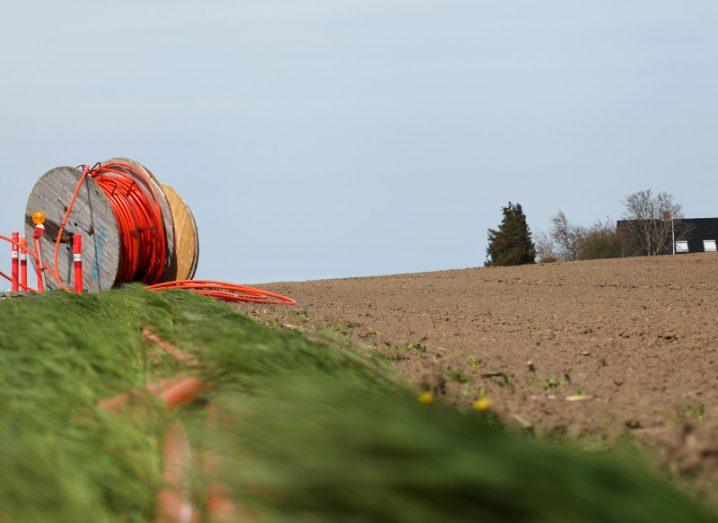 A roll of bright orange fibre cable on top of a hill going towards a rural home.