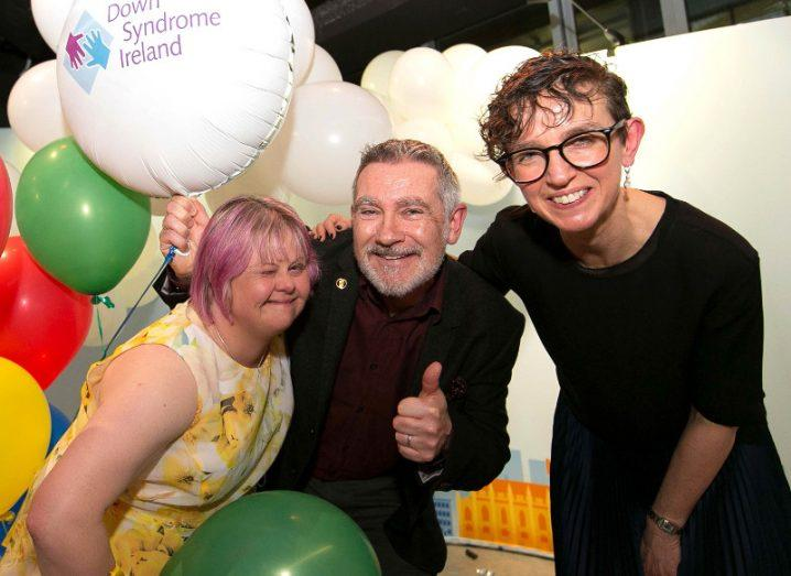 Two women and a man surrounded by balloons celebrating.