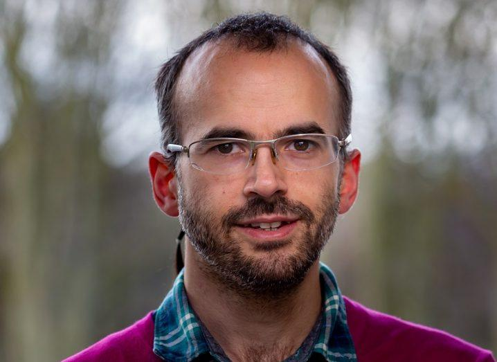Konstantinos Gkrintzalis wearing glasses and a purple jumper against a blurry tree background.