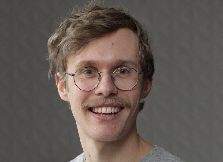 Headshot of Hayden Wilkinson, a moustachioed young man in spectacles with a bright smile.