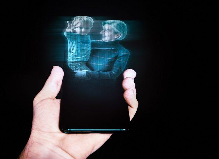 Person holding a phone with a 3D hologram of a woman and child being projected from it.
