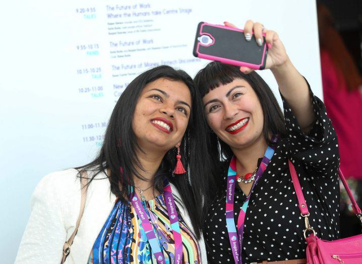 Two smiling women wearing Inspirefest lanyards pose for a selfie one of them is taking with her phone.