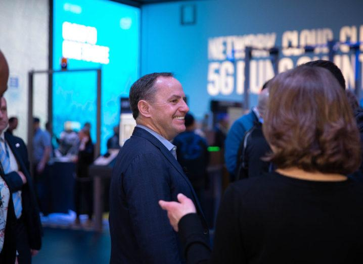 Man in suit smiling and talking at Mobile World Congress.