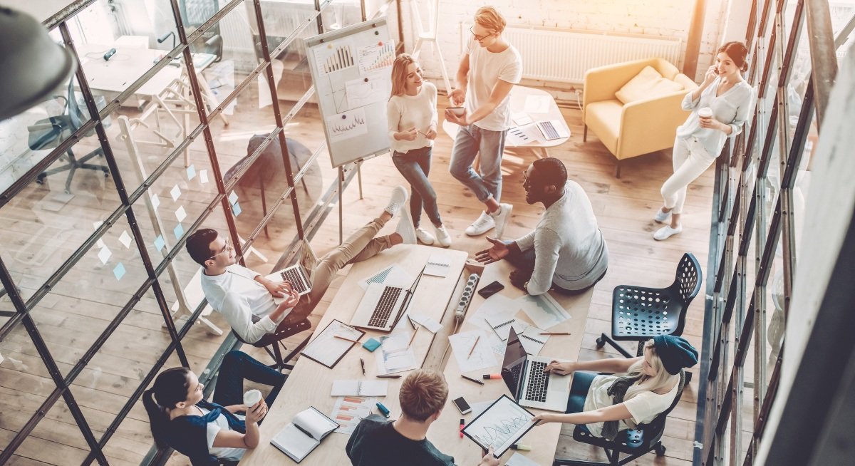 An elevated view of a group of employees in an office boardroom using different methods of communication.