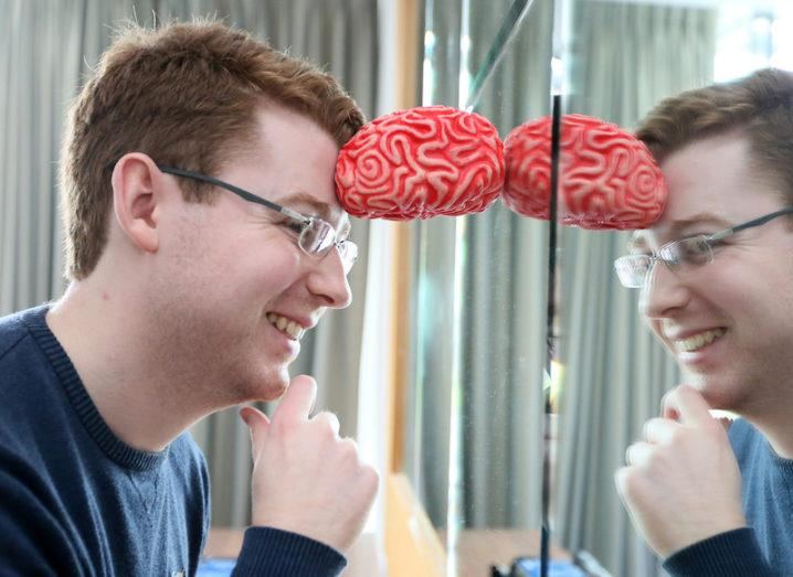 James Blackwell leans into his reflection in a mirror, propping his head up against a small model of the brain.