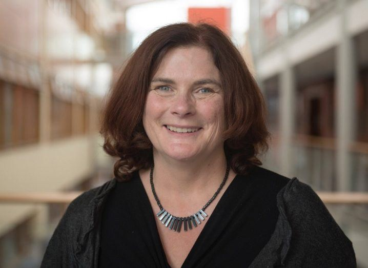Jane Suiter smiling and wearing a black top in the interior of the DCU campus.