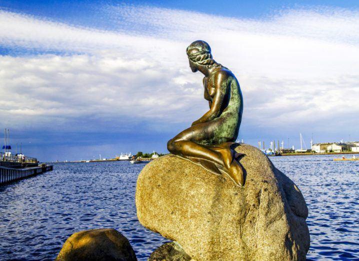 Little Mermaid statue in Copenhagen under a blue cloudy sky.
