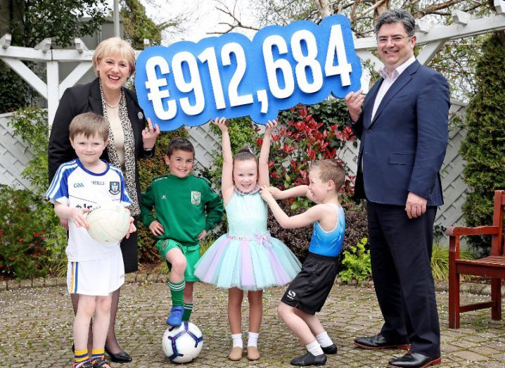 Two adults and four children hold up a sign showing the amount of 912,684 euro.