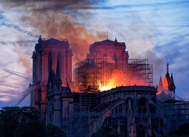 The Notre Dame cathedral on fire against a sky with a setting sun.