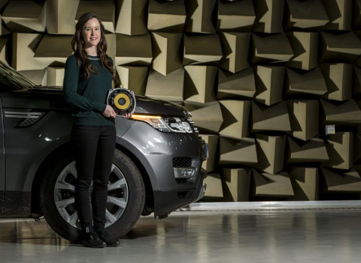 Orla Murphy smiles and holds a piece of in-car acoustic equipment as she stands in front of a Jaguar Land Rover.