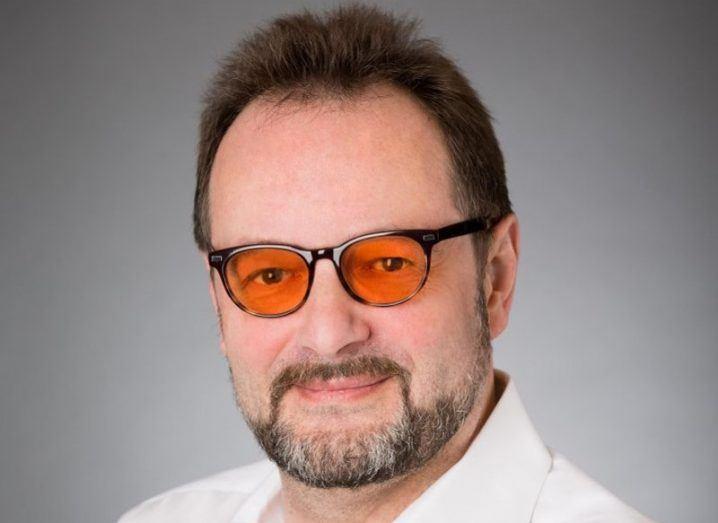 Man with dark hair, greying beard and white shirt wearing orange tinted glasses.