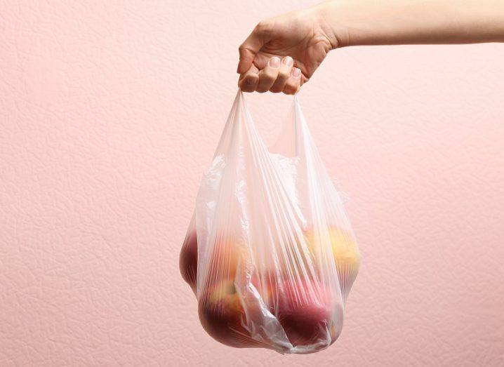 Close-up of a woman holding a plastic bag with red apples against a pink background.