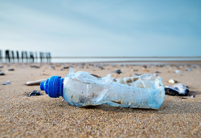 Close-up of an empty waste plastic bottle washed up on a beach with other plastic waste.