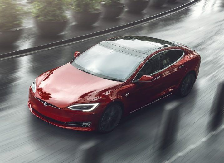 A red Tesla Model S driving on a wet road with concrete and plant bollards either side.