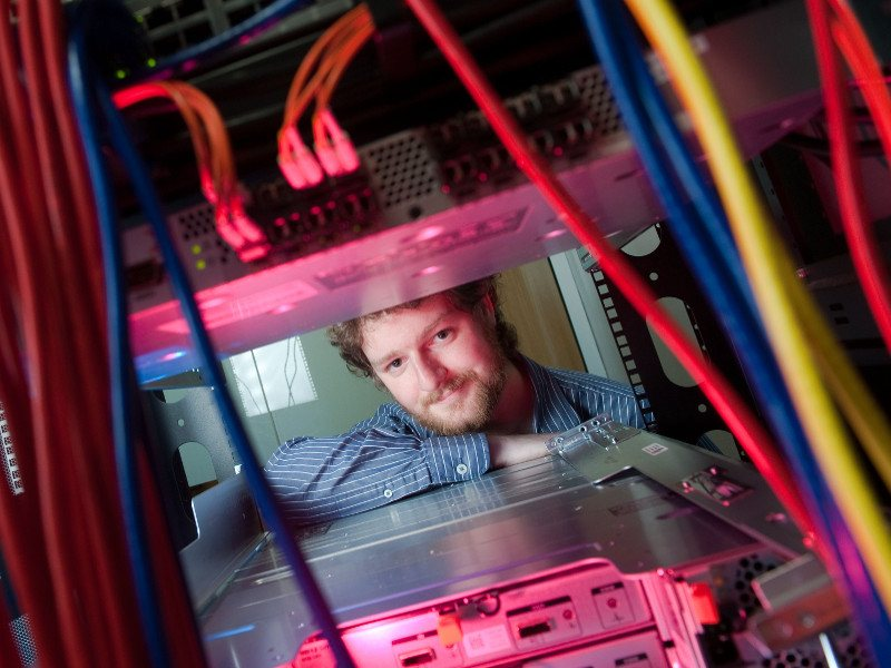 Man with brown hair and beard pokes his head through a server rack.
