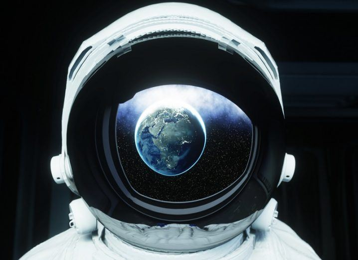 Close-up of an astronaut wearing a spacesuit helmet with Earth visible in its reflection.