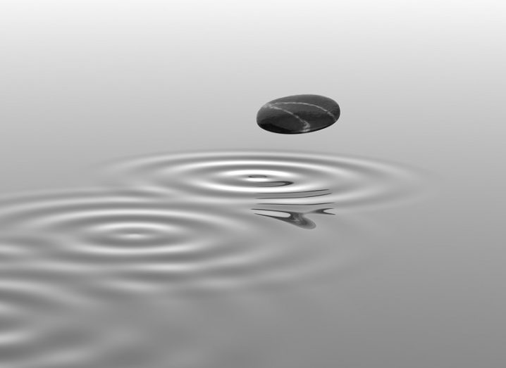 Greyscale image of a rock skipping across water leaving a trail behind it.