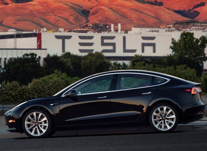 A dark blue Telsa Model 3 parked in front of one of the company's factories.
