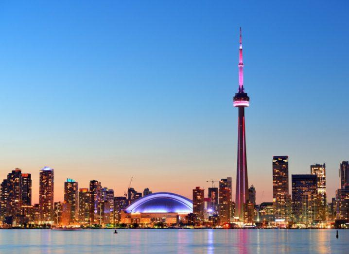 The Toronto city skyline at night under a blue sky with buildings lit up.