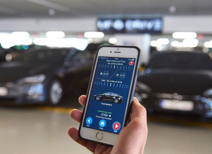 A hand holding a smartphone with a car rental app in front of parked electric cars.