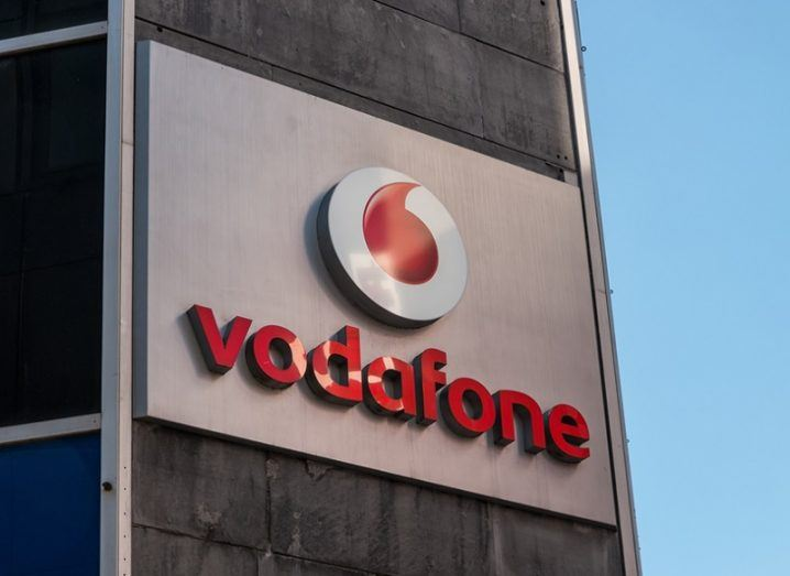 A Vodafone logo on the side of a grey building.