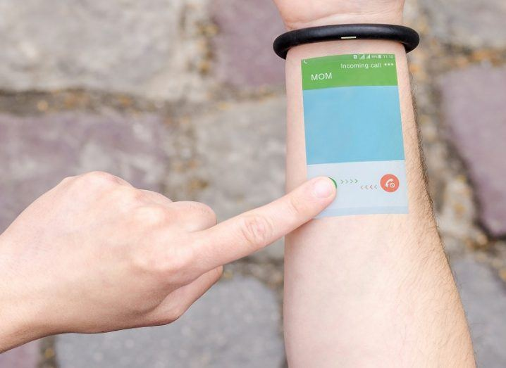 Concept of a person with a wearable bracelet projecting an interactive phone screen on their arm.