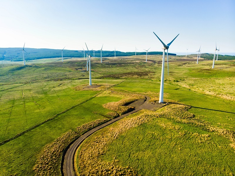 Aerial view of wind turbines surrounded by grass against a blue sky.