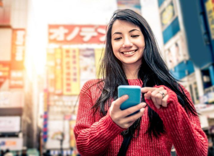 Woman smiling in a red jumper playing a game on her phone in Tokyo.