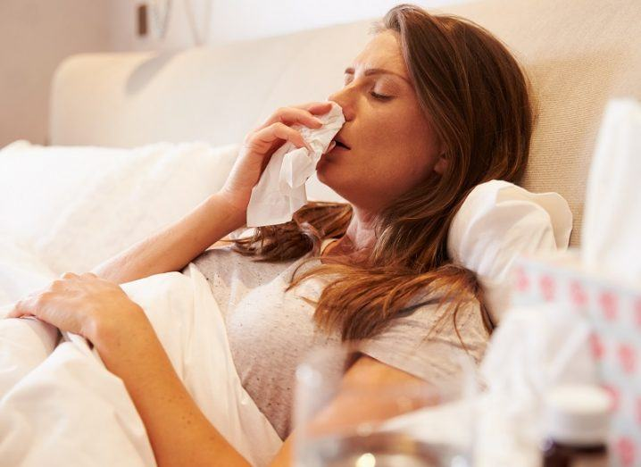 Woman suffering from the flu blowing her nose while lying down in bed.