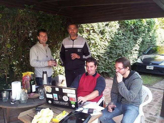 Co-founders of a start-up stand around a laptop in the garden, drinking beer.