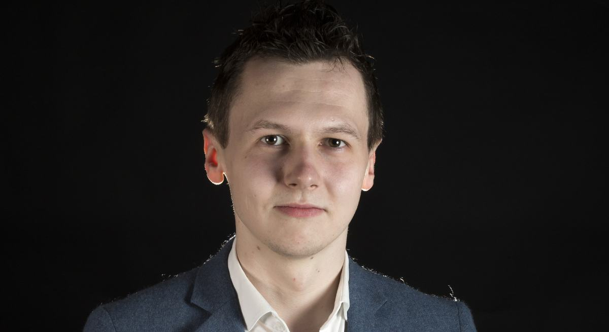 Inspirefest 2019 speaker Adam Harris, a young brown-haired man pictured against a black background.