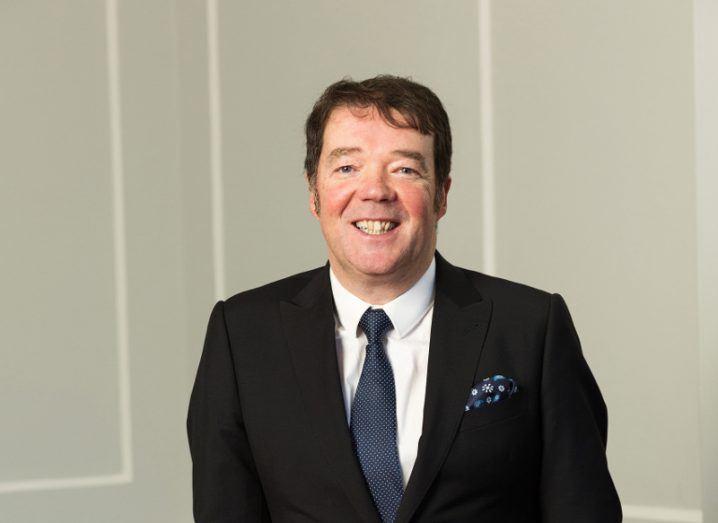 man with dark hair wearing white shirt, blue tie and dark blazer standing against a white wall.