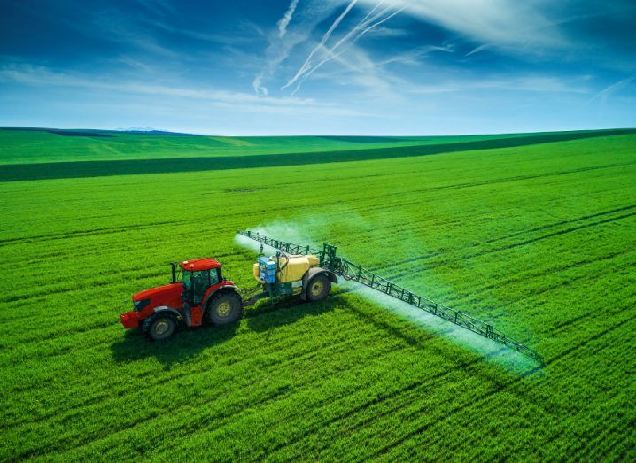 A red tractor in a green field under a cloudy blue sky.