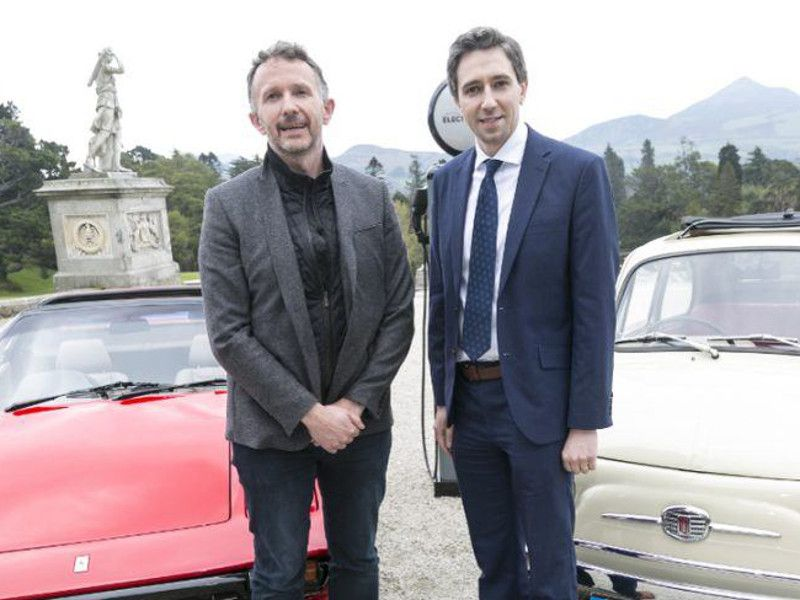 Two men in suits stand in front of a pair of classic cars.