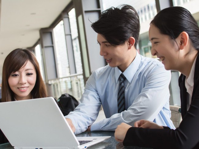 A group of workers in Japan gathering around a computer for training.