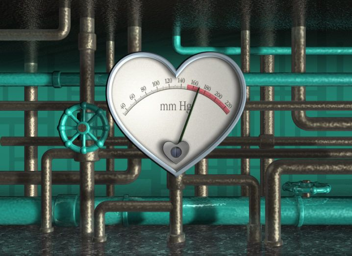 Picture of a heart-shaped meter surrounded by green-coloured pipes and valves.