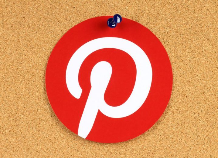 Pinterest logotype printed on paper and pinned on cork bulletin board.