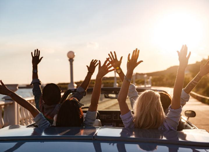 Back view of happy young friends driving in cabriolet with raised hands on sunset.