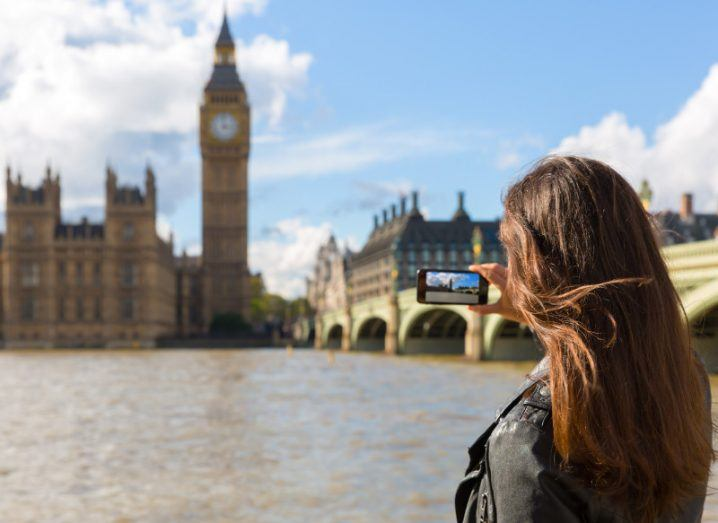 Woman with a leather jacket takes a picture of Big Ben with her smartphone in London, symbolising roaming.
