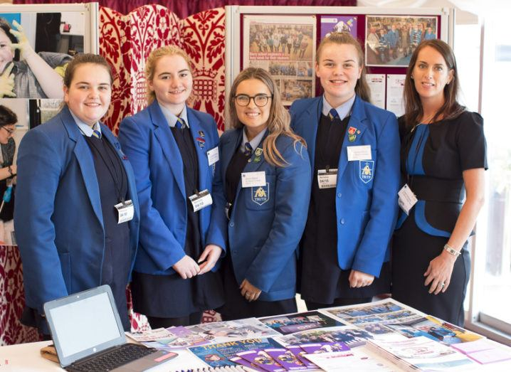 A row of four teenage girls in school uniforms and a woman stand in front of a display of Engineers Week materials.