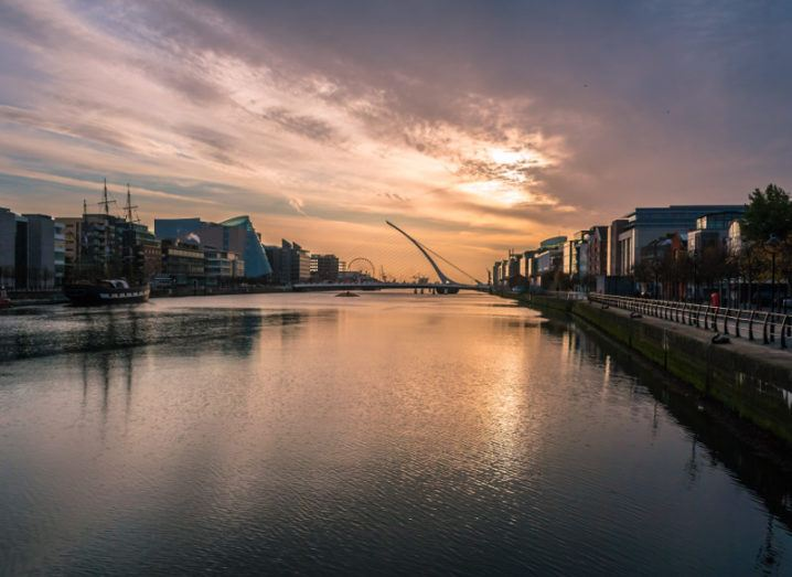 Dawn breaks over Ireland's financial district in the Dublin docklands with sun glinting off River Liffey.