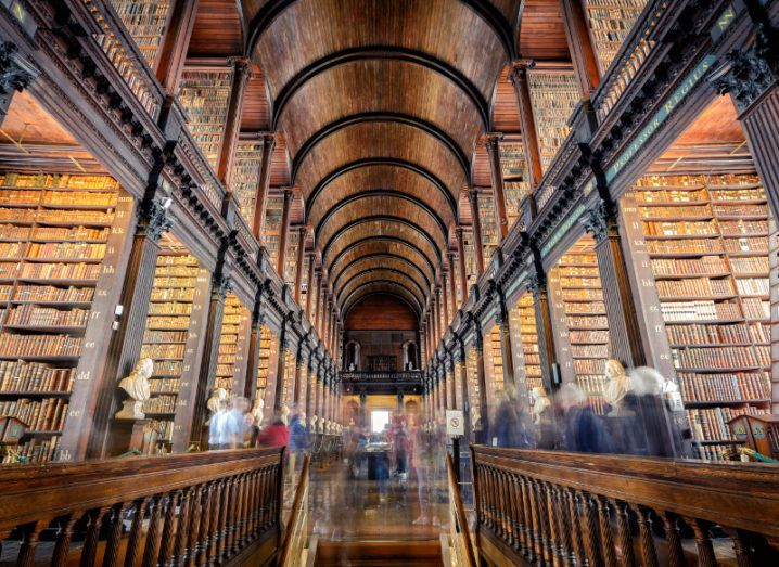 Inside the iconic Trinity College library of Dublin with people moving around the various aisles.