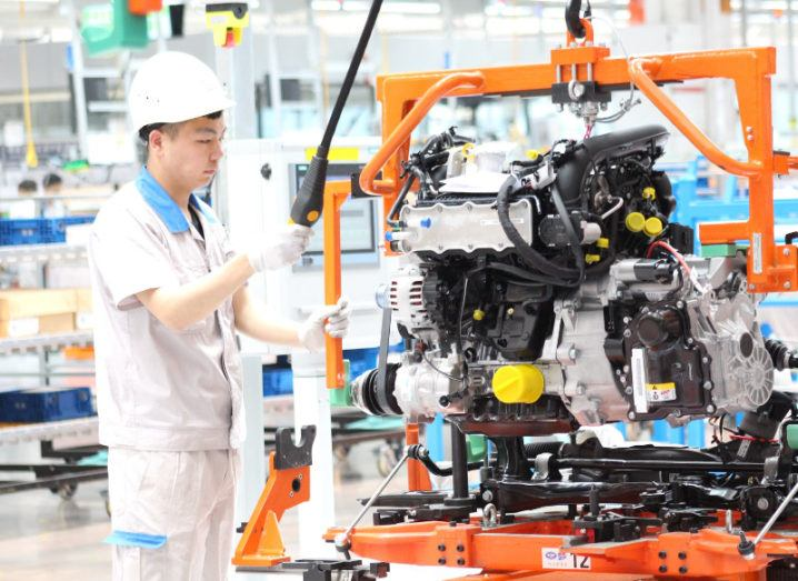 A worker on the floor with a Volkswagen engine in China.