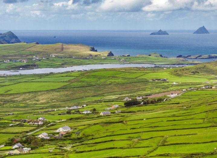 A view of lush green fields, the Atlantic ocean, Valentia island and the Skellig islands in County Kerry, Ireland.