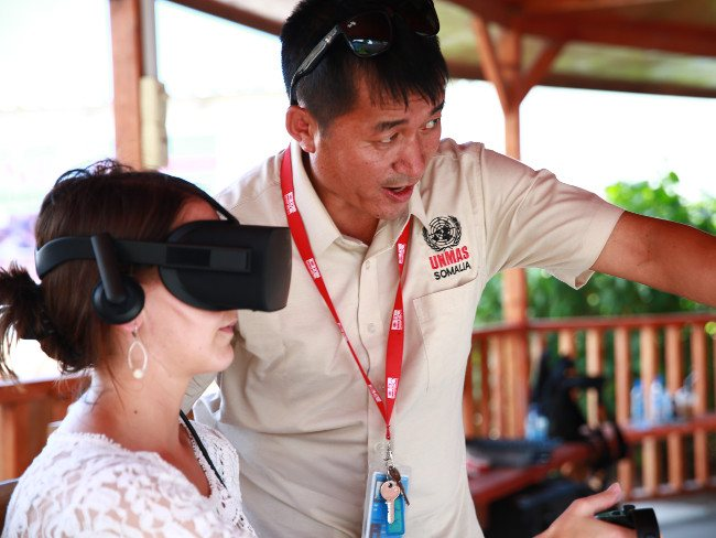 Woman wearing VR headset while an instructor in white shirt explains what she is seeing.