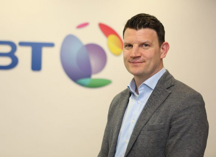 Image of a brown-haired man in a dark grey suit standing and smiling in front of colourful BT logo.