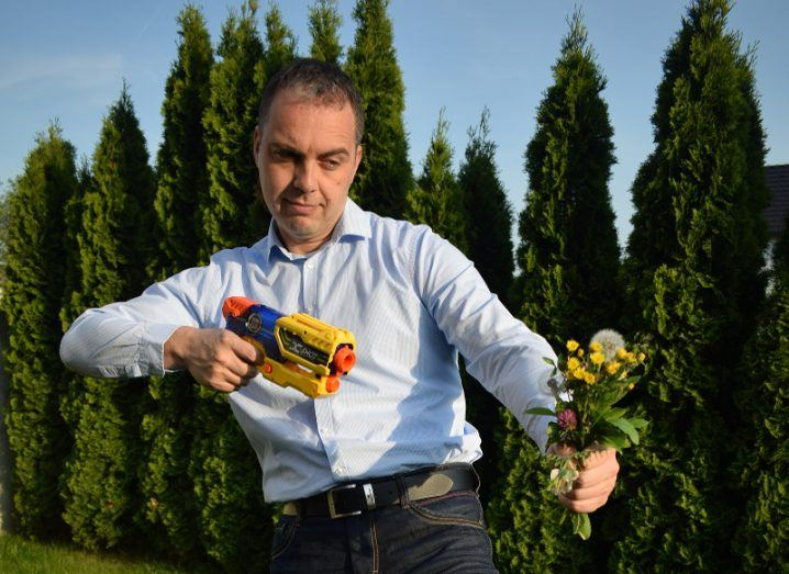 Dark haired man points a toy gun at a bunch of weeds.