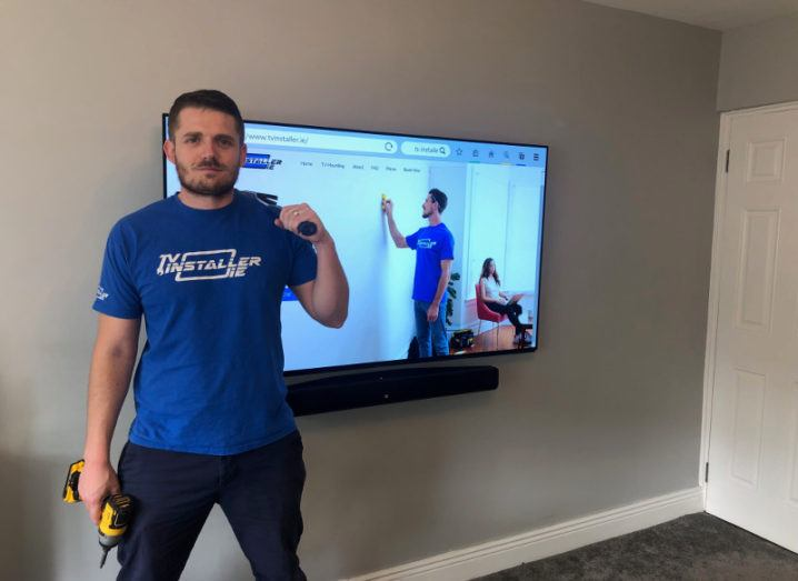 Man in blue t-shirt holding a power drill beside a newly installed flatscreen TV.