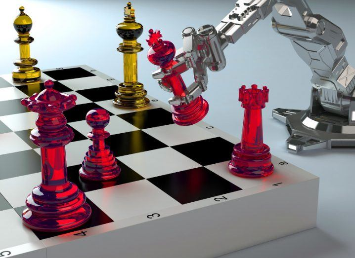 silver robotic arm lifts a red king chess piece over a chess board on a bright white surface, symbolising AI.